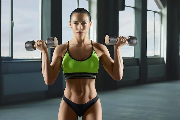Woman bodybuilder lifting metallic dumbbells.