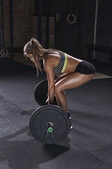 여성 보디빌더는 체육관에서 바벨 운동을 할 준비를 합니다.