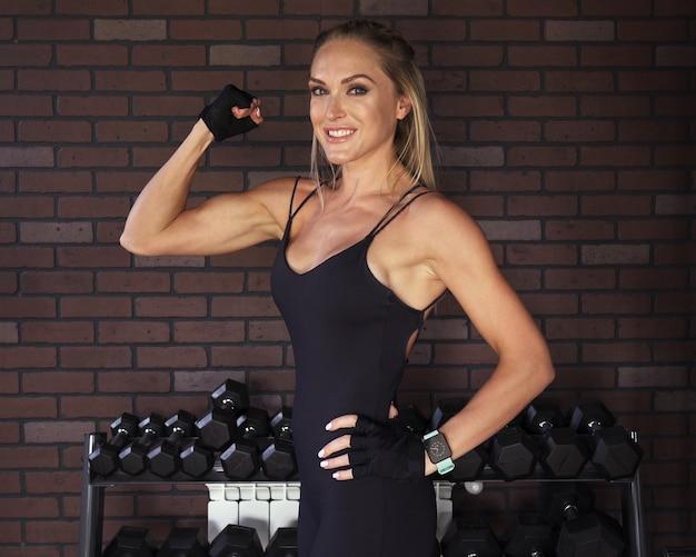 체육관에서 벽돌 벽에 팔뚝을 보여주는 여자 보디