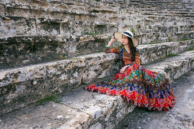 Woman in bohemian dress sitting on theater of hierapolis ancient city in pamukkale, turkey.
