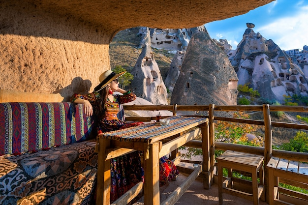 Woman in bohemian dress sitting on traditional cave house in cappadocia, turkey.