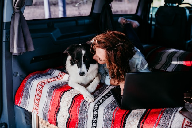 Woman and border collie dog in a van. woman working on laptop. travel concept