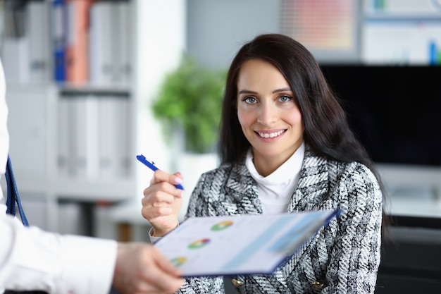 Женщина-босс держит ручку, чтобы исправить отчет