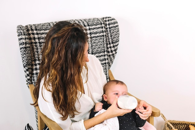 Woman bottle feeding baby in armchair Premium Photo