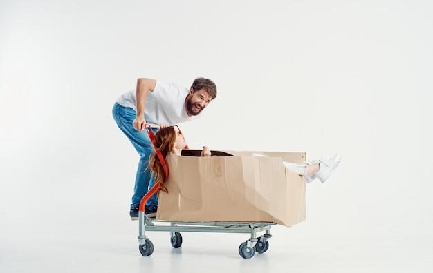 Woman in a box on a cargo trolley and a cheerful male courier on a light background