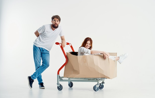 Woman in a box on a cargo trolley and a cheerful male courier on a light