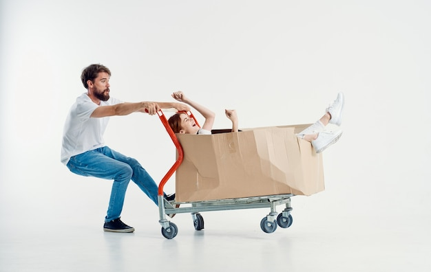 Woman in a box on a cargo trolley and a cheerful male courier