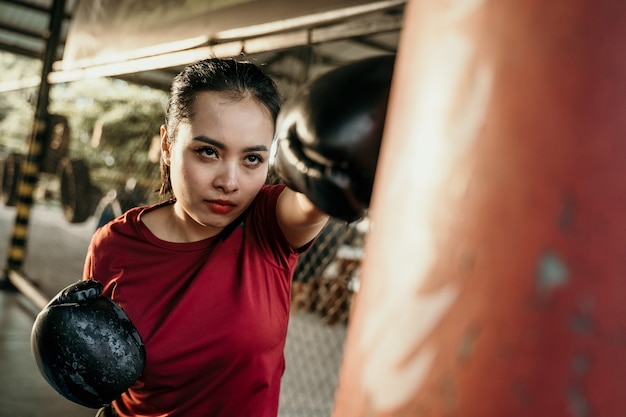 Woman boxer fighter doing exercise hitting punching bag with copyspace at boxing camp