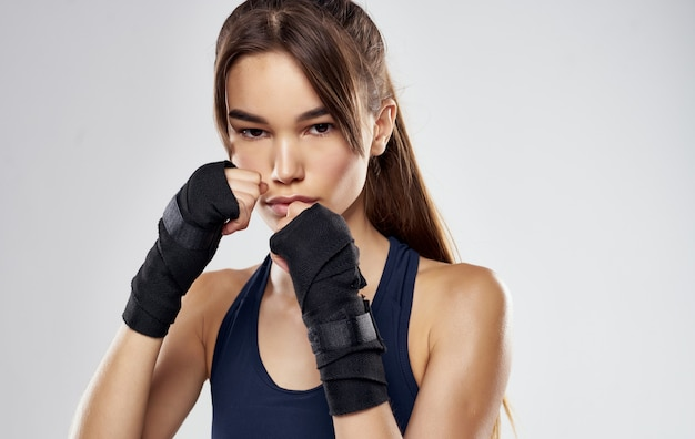 Woman boxer in gloves on gray cropped view of brunette model.