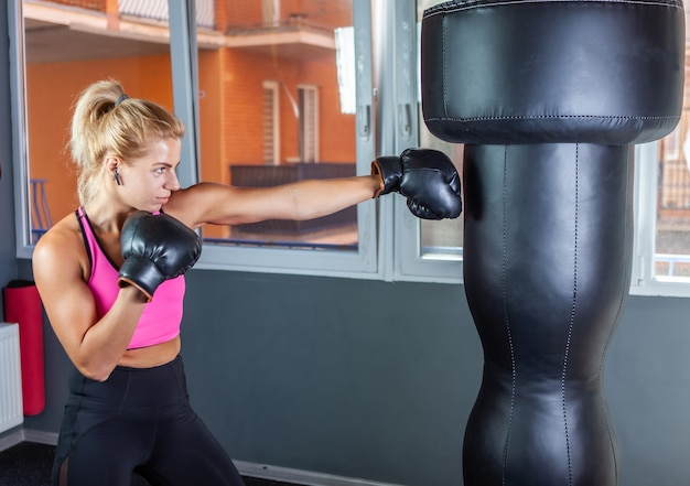 ボクシンググローブの女性ボクサーはサンドバッグをパンチします