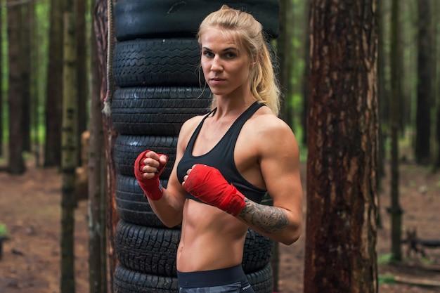 屋外でワークアウトボクシングの姿勢でポーズをとる女性ボクサープロの戦闘機