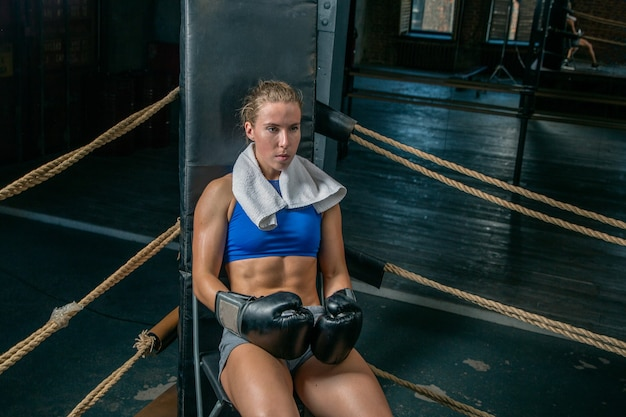 Woman boxer resting in the corner of the ring