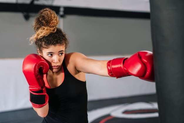 Woman boxer training with red boxing gloves punching directly into a punching bag in a gym