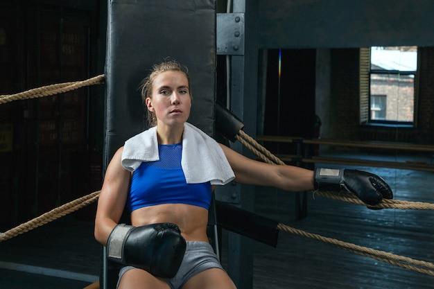 トレーニング後に休んでいる彼女の首の周りにタオルを持つ女性ボクサー