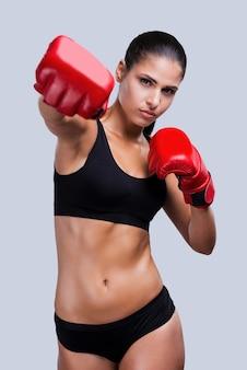 女子ボクシング。灰色の背景に立っている間ボクシングの美しい若いスポーティな女性