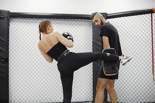 Boxe donna. principiante in palestra. signora in abbigliamento sportivo nero. donna con allenatore.