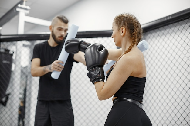 Woman boxing. beginner in a gym. lady in a black sportwear. woman with coach.