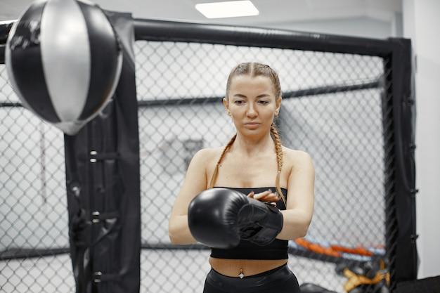 Boxe donna. principiante in palestra. signora in abbigliamento sportivo nero.