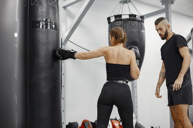 女子ボクシング。ジムの初心者。黒のスポーツウェアの女性。コーチを持つ女性。