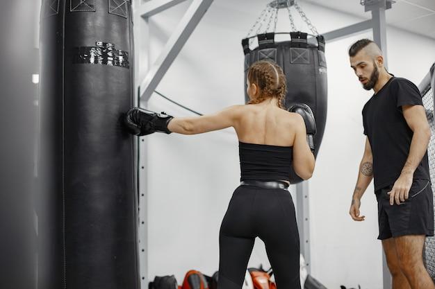 여자 권투. 체육관에서 초급. 검은 sportwear에있는 여자. 코치와 여자입니다.