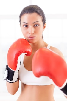 Женский бокс. уверенно молодая женщина в боксерских перчатках, глядя на камеру