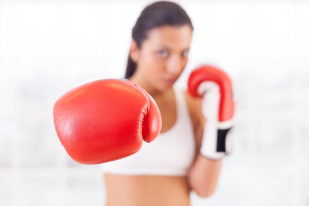 Женский бокс. уверенно молодая женщина в боксерских перчатках протягивает руку и смотрит в камеру