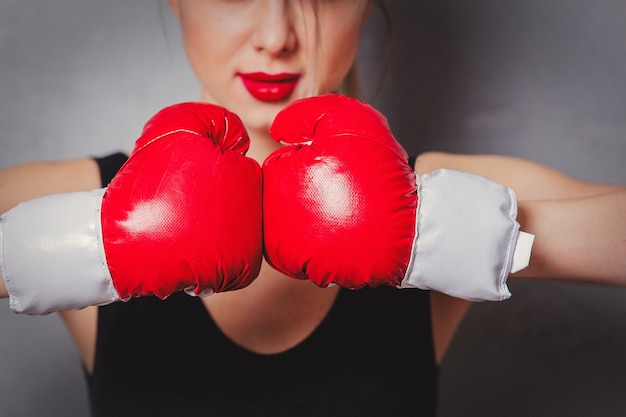 Woman in boxing gloves on gray background