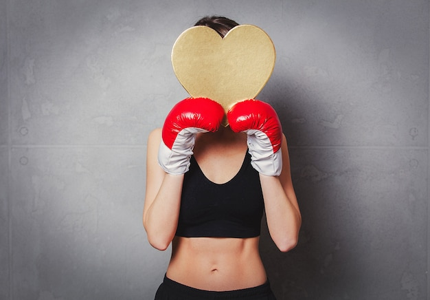 Woman in boxing gloves with heart shape gift box in hands