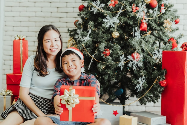 Woman and boy sitting together by christmas tree with gift boxes