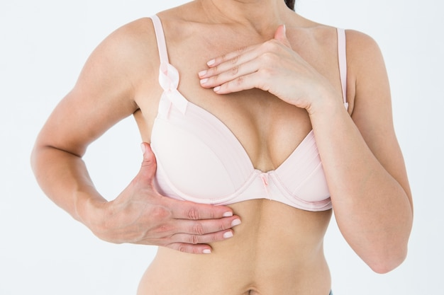Woman in bra with breast cancer awareness ribbon