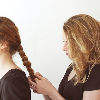 Woman braiding her sister hair against white backdrop