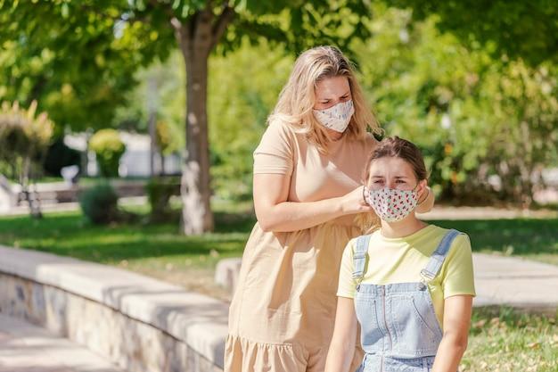パンデミックの最中に女性が公園で友人の髪を編む