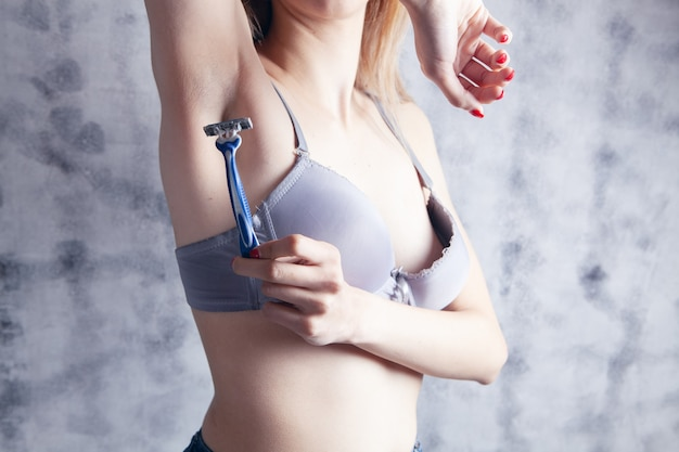 Woman in bras shaves her armpit with a razor