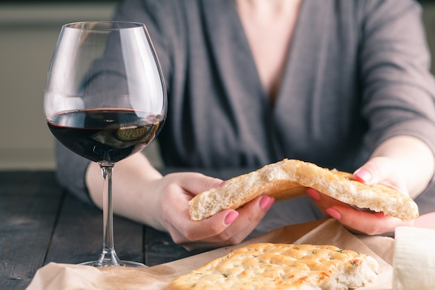 Woman break bread and drinking red wine