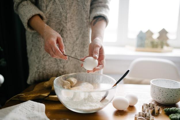 女性は卵を割って小麦粉に加えます。プロセスクッキング。
