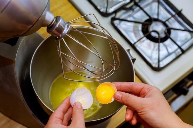 女性は金属製のボウルに卵を割る