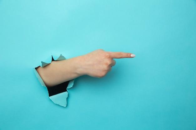 여자가 종이 파란색 벽을 뚫고 팔을 뚫고 오른쪽 빈 공간에 조언을 제공합니다.