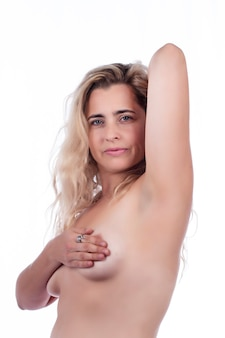 Woman breast self care and examination for lumps or weird symptoms over a white.