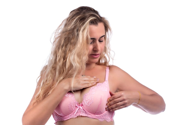 Woman breast self care and examination for lumps or weird symptoms, with pink bra over a white.