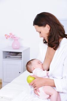 女性は彼女の赤ちゃんを授乳し、リンゴを保持