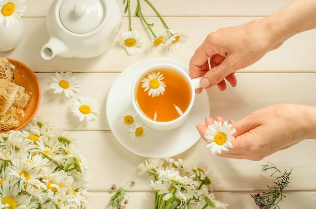 A woman brews herbal tea with chamomile.