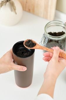 여자는 갈색 열 머그잔에 차를 끓여서 그녀와 함께 가져가는 귀여운 나무 숟가락을 들고 있습니다.