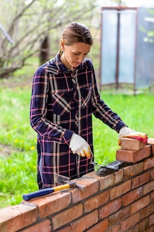 レンガの壁にこてでレンガ造りのセメントモルタルをレイアウトする女性の煉瓦工