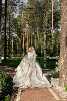 고급스러운 푹신한 웨딩 드레스의 여자 신부는 결혼식 경로를 따라 실행됩니다.