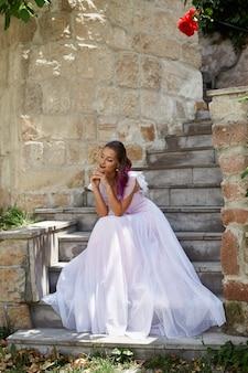 女性の花嫁は階段に座って、彼女の新郎を待っています