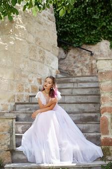 女性の花嫁は階段に座って、彼女の新郎を待っています。
