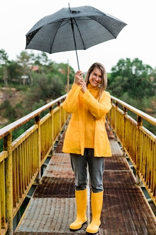 Woman on bridge holding an umbrella