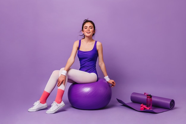 Woman in bright fitness bodysuit sits on fitball on wall of yoga mat, pink water bottle and dumbbell