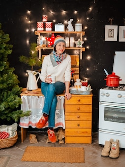 Woman bright hat kitchen stove. girl prepares winter evening. wooden rustic kitchen