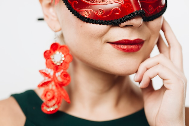 Woman in bright red carnival mask